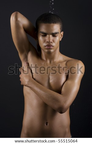 Drops of the water on naked body of a young man on black background.