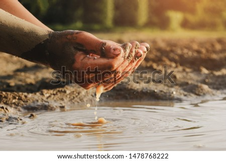 Drops of water falling from kid hand on Crack dried soil background, Affected of global warming made climate change. Water shortage in worldwide and drought concept.