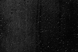 Drops of water flow down the surface of the clear glass on a black background. Texture for creativity.