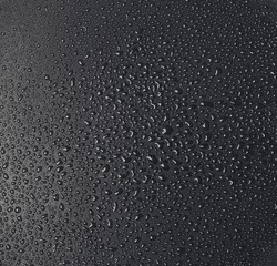 Drops of water on a dark matte surface close up.