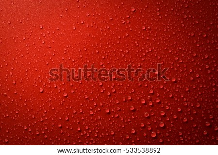 Stock Photo Drops of water on red and black surface. Macro photo, drop, shadow plastic base.