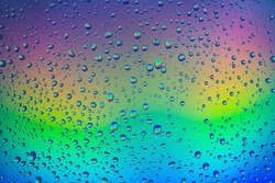 Drops of water on the glass with colorful rainbow background. Morning dew on the window with a refractive reflection of multi colored sunlight.