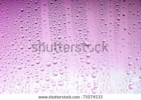 Drops on a glass surface with a pink or red color gradient