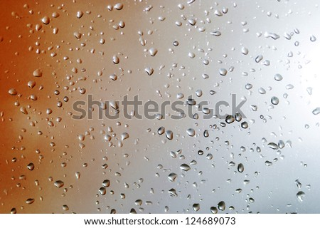 Drops on a glass with a orange gradient and sunlight.