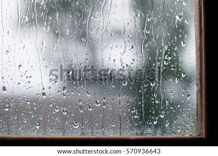 drops on the glass in rainy day. close up, the background mode. rain outside the window on summer or autumn day.