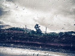 Drops on window with sad landscape in blackground. Melancholy sad day rainy sadness concept