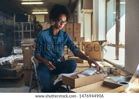 Dropshipping business owner working, checking order to confirm before sending to customer. Female entrepreneur packaging box for delivery. #1476944906