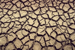 Drought arid and cracked earth weather in dam or river, hot summer nature, cracking soil full flame photo, surface clay soil rough crack pattern texture background, desert broken hot mud ground