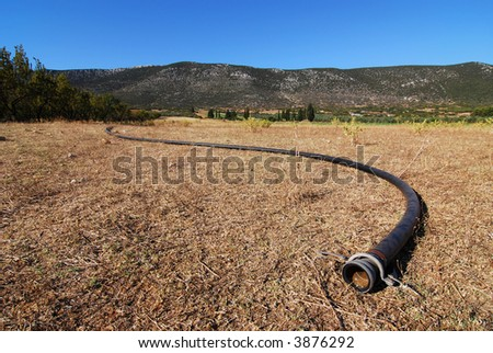 drought implied with dry water pipe on arid farmland
