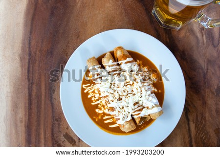 Drowned Mexican flutes, traditional Mexican food with red sauce. Drowned tacos. Traditional Mexican food. Mexican food on wooden background. Traditional food concept. Foto stock ©