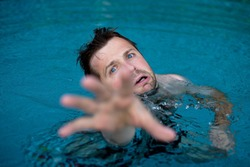 Drowning caucasian man in swimming pool asking for help. He stretching his hands in fear. Emotional stress in dangerous situation. Do not know how to swim.