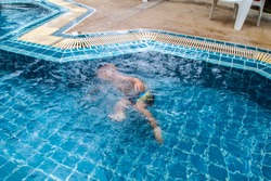 Drowning child in the pool. Watch your child by the water, danger of letting children play alone in pool.