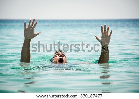 Drowning man in sea asking for help with raised arms. #370187477