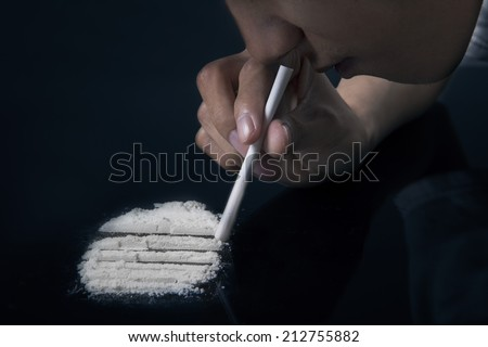 Drug abuse, man taking drugs, snorting cocaine portrait