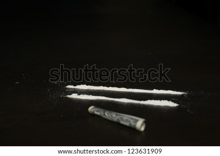 Drug abuse: Two rows of cocaine being prepared for sniffing with a dollar bill lying in the front