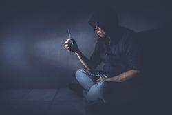 Drug addict man hold narcotic syringe Inside a dark room with drama color tone. Stop drug concept.