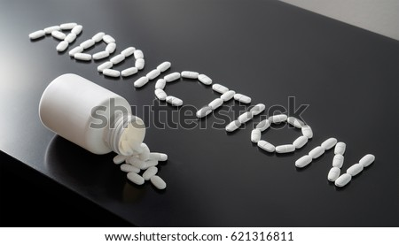 Drug addict or medical abuse concept. Obsession to pharmaceutical substances or narcotics or anxiety pills. Addiction written with white tablets. Medicine spilling out from a bottle on a dark table.