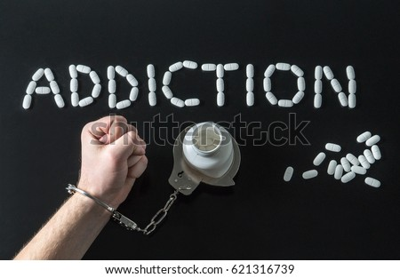 Drug addict or medical abuse concept with man handcuffed to a medicine bottle. Obsession to pharmaceutical substances or narcotics or anxiety pills. Addiction written with tablets on dark background.