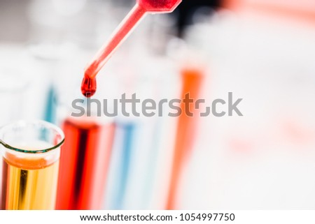 drug discovery, pharmacology and biotechnology concept. test tube and pipette with a sample drop. laboratory science background.