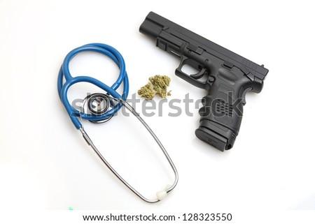 Drug Trade vs. Harm Reduction/Stethoscope, marijuana buds & handgun against white background.