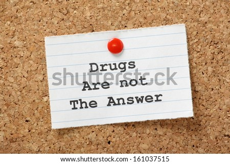 Drugs Are Not The Answer in typescript on a lined paper note pinned to a cork notice board