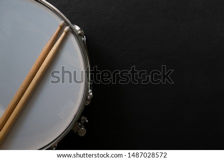 Drum stick and drum on black table background, top view, music concept
