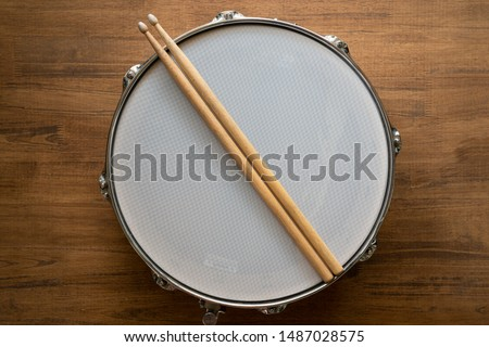 Drum stick and drum on wooden table background, top view, music concept