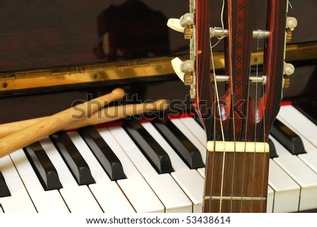 Drum sticks, guitar and piano keyboard. For concepts like music composition and creativity.