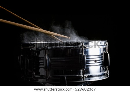 Drum sticks hit on the snare drum in black background, close-up, low key