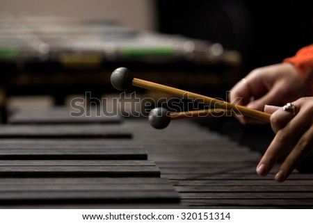 Drum sticks striking the xylophone in close up in dark colors
