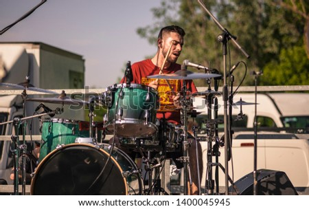Drummer on the move while banging his drum sticks to play #1400045945