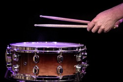 Drummer playing drum sticks on a snare drum on black background close up.