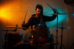 Drummer playing drums in recording studio, with orange and cyan lighting, using flame-patterned wooden drumsticks, with dreadlocks and beard, wearing black zip-up hoodie
