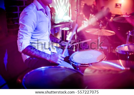 Drummer playing on drum set on stage. Warning - Focus on the drum, authentic shooting with high iso in challenging lighting conditions. A little bit grain and blurred motion effects. #557227075