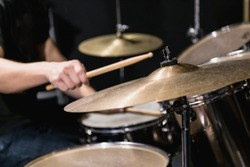 Drummer plays with drumstick at music studio