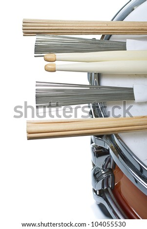 Drumsticks,brushes and unplugged sticks resting on a cherry sunburst colored snare drum, shown only a part of its side and top with the metal rim- isolated on white