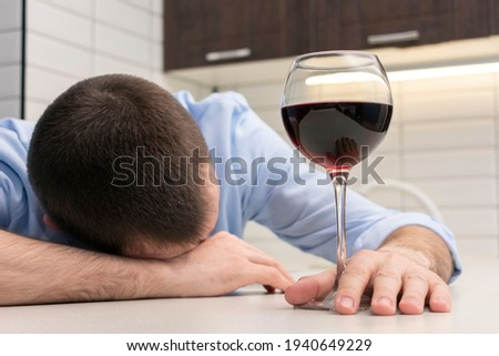 Drunk alcohol man and wine glass at home, man suffering alcoholism problem and addiction intoxicated, close-up ストックフォト ©