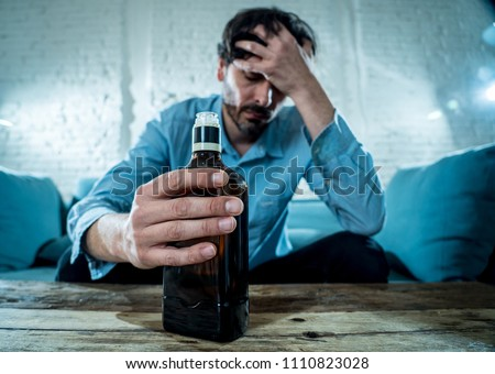 drunk alcoholic lain business man drinking whiskey from the bottle and glass depressed wasted and sad at home couch in alcohol abuse and alcoholism concept #1110823028