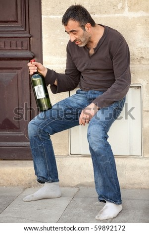 drunk alcoholic man standing near house entrance in the city