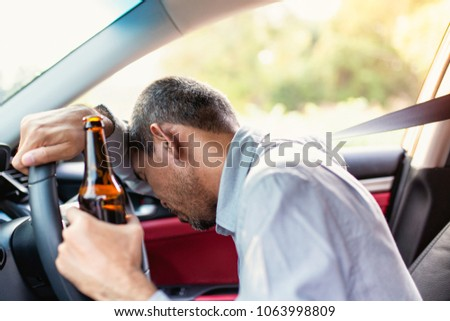 Drunk asian young man drives a car with a bottle of beer with sunset background, Dangerous driving concept #1063998809