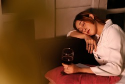 Drunk business woman fall asleep after drinking red wine too much.