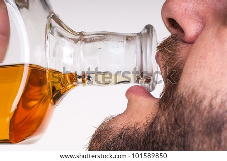 Drunk businessman drinking from a bottle of whisky