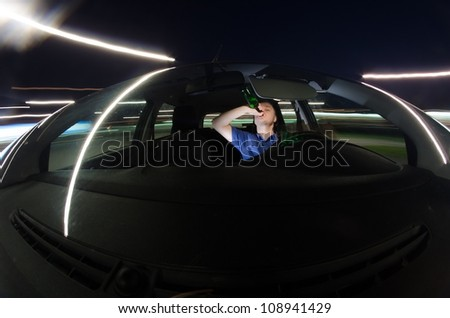 Drunk driver drinking alcohol while driving a car at night