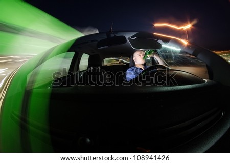 Drunk driver drinking beer while driving a car at night