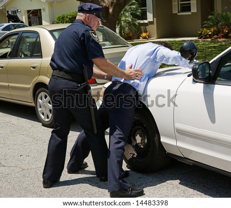 Drunk driver spread eagle on the police car, being patted down.