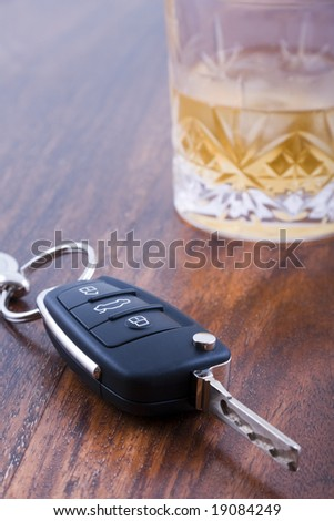 Drunk driving concept - car keys on table with glass of whiskey