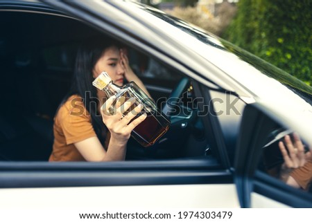 Drunk female driver in car, Bottle of alcohol in a woman's hand behind the steering wheel - a concept of driving intoxicated ストックフォト ©