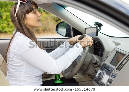 Drunk female driver trying to judge her distances clutching her bottle of booze between her thighs and rising up to peer over the dashboard