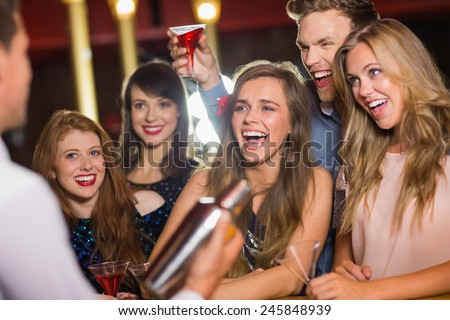 Drunk friends watching barman making cocktail at the nightclub