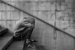 Drunk homeless unhappy man covered his face with his hands and sits on the stairs in the underpass, black and white photo.